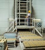 Man in a safety hat performing check on a factory