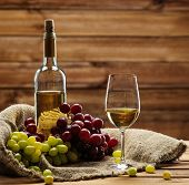 Bottle of red white, glass and grape on a sack in wooden interior