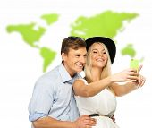 Beautiful smiling young couple making selfie against world map
