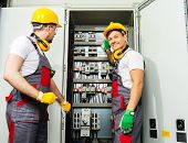 Two electricians in a safety hat and headphones on a factory