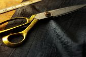 Measuring and cutting textile or fine fabric. Work table of a tailor. Gold scissors and black fabric.