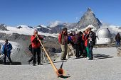 Swiss man blowing traditional alpine horn on Matterhorn mountain