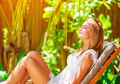 Cute female on tropical resort, sitting on deckchair with closed eyes and taking sun bath, enjoying