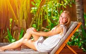 Cute female on tropical resort, sitting on deckchair and taking sun bath, enjoying exotic nature, su
