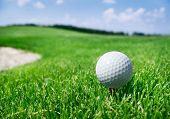 Golf ball on a tee against golf course