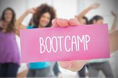 Woman holding pink card saying bootcamp against fitness class in gym