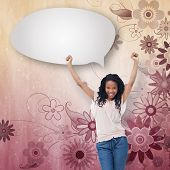 A young happy woman stands with speech bubble against digitally generated girly floral design