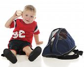 A young preschooler ready to toss the baseball he's just pulled from his sports bag.  On a white bac