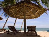 Sun Loungeres And  Umbrellas Against  Blue Sea At Sun Day Mui Ne, Vietnam