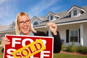 Beautiful Female Holding Keys & Sold Real Estate Sign