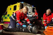 Paramedical team assisting injured man motorbike driver at night