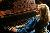 Baroque woman playing on an old grand piano