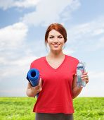 fitness, home and diet concept - smiling teenage girl with bottle of water and yoga mat after exerci