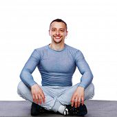 Happy sportsman sitting in the lotus position over white background