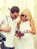 summer holidays, dating, city break and tourism concept - couple with map, camera and travellers gui