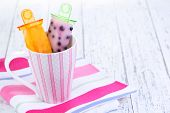 Fruit ice cream in cup on wooden table close-up