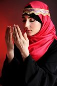 Beautiful muslim arabic woman praying on dark color background
