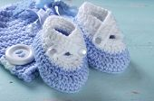 picture of teething baby  - Baby boy nursery blue and white wool booties and bonnet close up on aqua vintage shabby chic background for baby shower or newborn girl greeting card - JPG