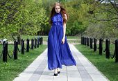 Young beautiful girl in a blue dress walk in the summer park