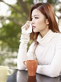 pic of grieving  - young woman wiping tears with facial tissue - JPG