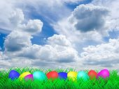 Easter Eggs lying on a meadow with the sky and clouds in the background