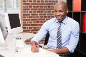Portrait of smiling young businessman writing document at office desk