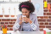 Female interior designer drinking coffee at office desk