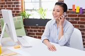 Smiling female executive using mobile phone at office desk
