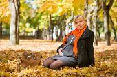pregnant woman with handbag in autumn park