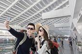Asian couple travel and selfie in the Taipei Taoyuan International airpor, Taiwan.