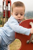 stock photo of seesaw  - Portrait of a child climbing a playground seesaw - JPG