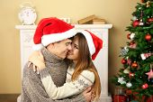 Nice love couple near Christmas tree. Woman and man celebrating Christmas