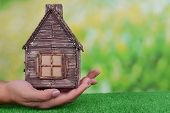Woman hands holding small house on grass on bright background