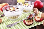 Oatmeal in bowls, yogurt, apples and walnuts on napkin on brown wooden background