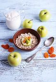Bowl of oatmeal, dried apricots, apples and yogurt on blue wooden background