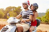 picture of scooter  - Young Couple Riding Motor Scooter Along Country Road - JPG