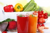 Vegetable juice and fresh vegetables  on wooden table on natural background