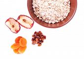 Bowl of oatmeal, dried apricots and raisins isolated on white