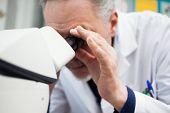 Scientist using a microscope in his laboratory