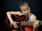 A Pretty Little Girl Playing Guitar