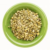 chamomile herb on an isolated green bowl