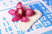 Sanitary pad and lilac orchid on blue calendar background