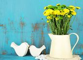 Yellow and green flowers in decorative jug on color wooden background