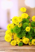 Beautiful bouquet of chrysanthemums flowers on wooden table, on light background