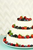 Beautiful wedding cake with berries on light background