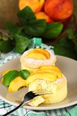 Tasty mini cakes with fresh peach, on table