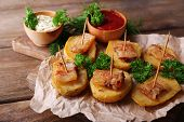 Baked potato with bacon on wooden cutting board, on wooden background