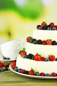 Beautiful wedding cake with berries on wooden table, on nature background
