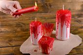 Process of decorating candles for Halloween party. Female hand holding burning candle, close-up