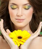 closeup portrait of attractive  caucasian woman brunette studio shot lips face hair head and shoulders skin makeup yellow flower eyes closed hands